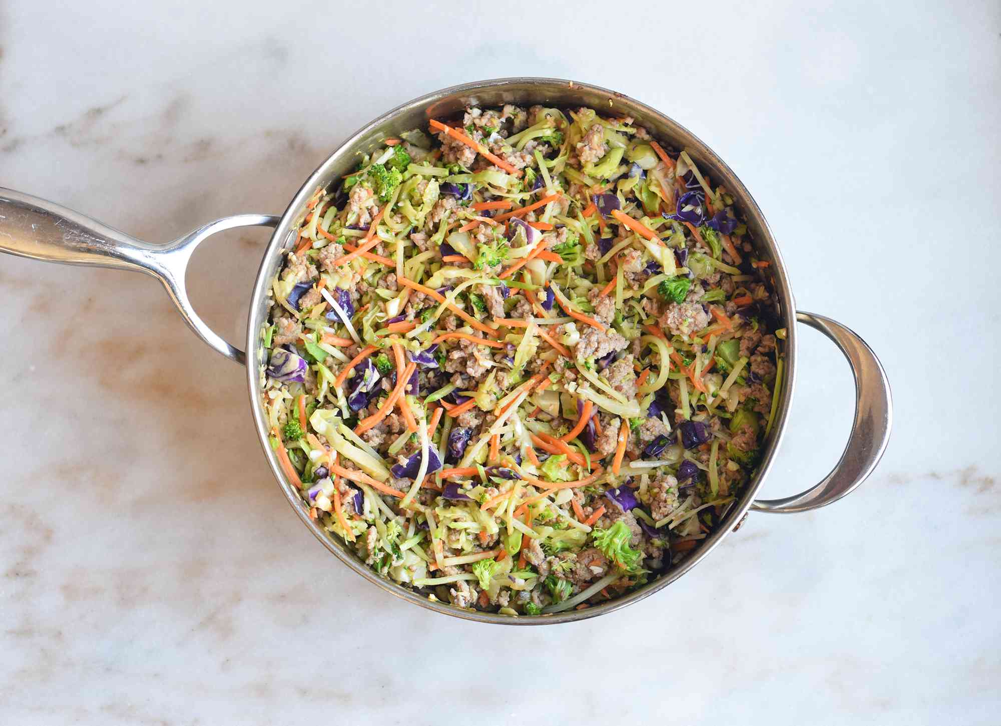 browned sausage and coleslaw mix in a saute pan