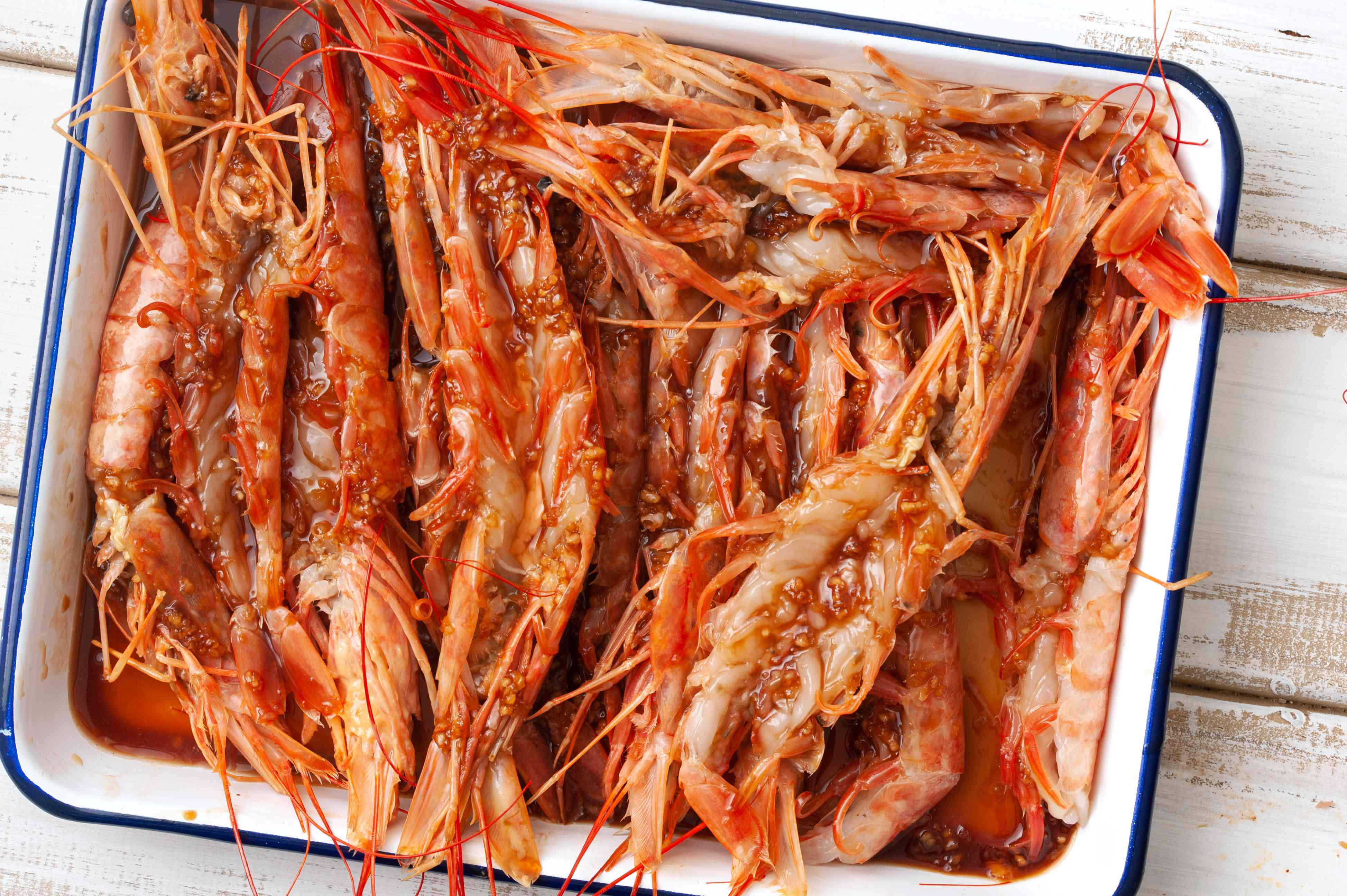 Shrimp arranged in baking dish, covered in marinade