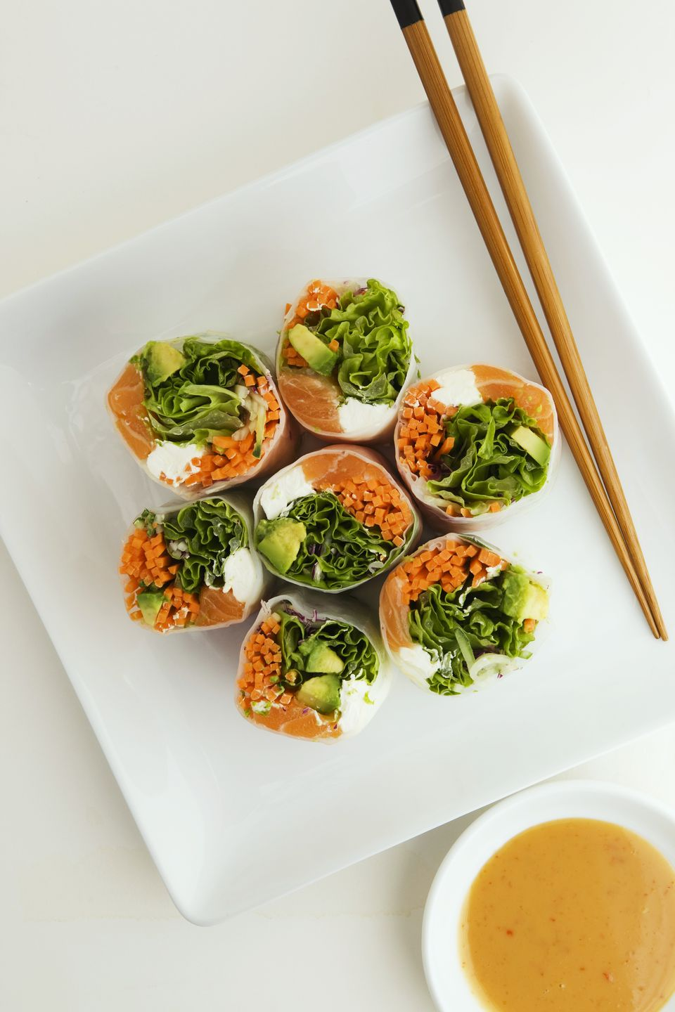 Salmon Rolls on a Plate with Chopsticks and Peanut Dipping Sauce