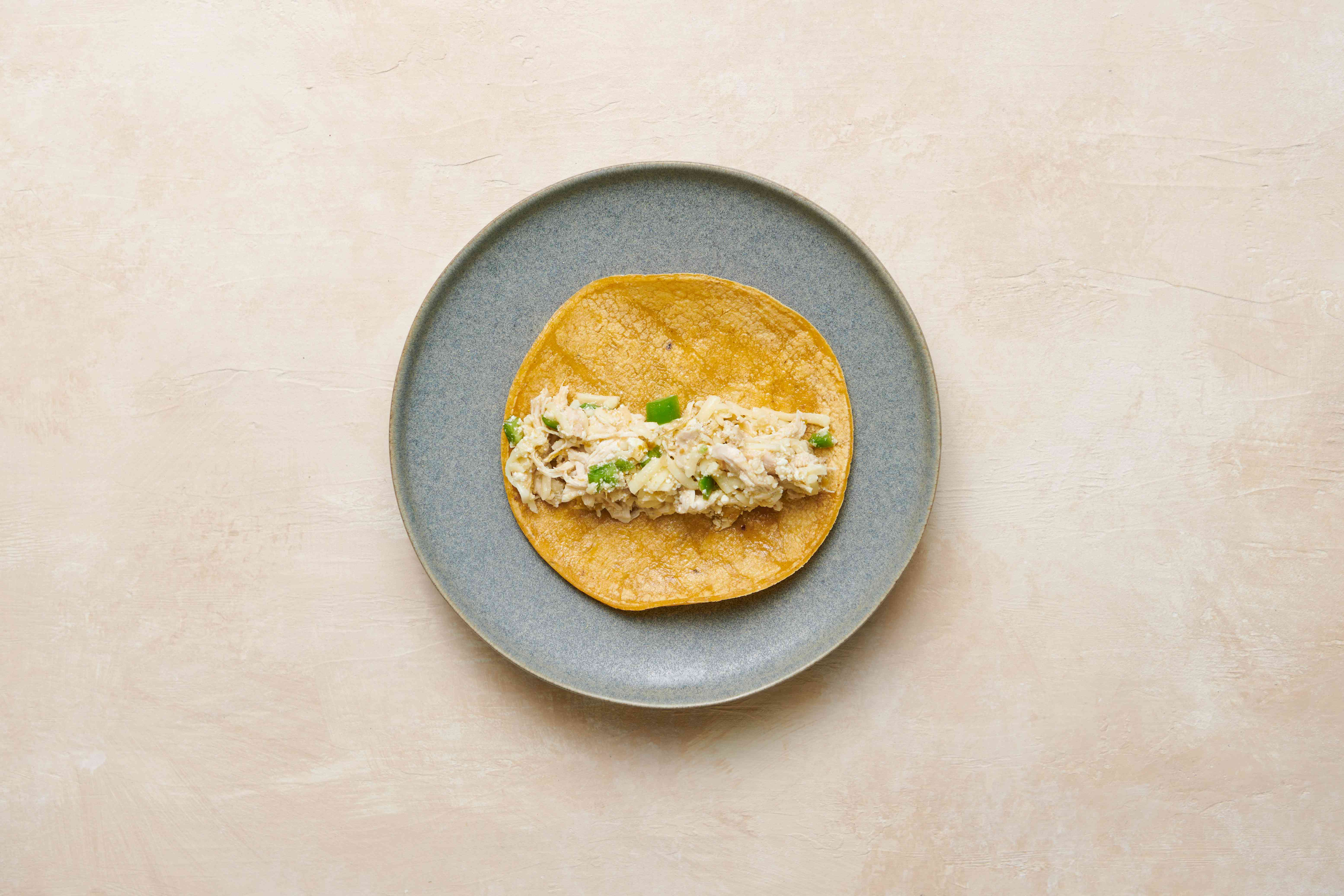 Tortilla with chicken chile filling on top, on a plate