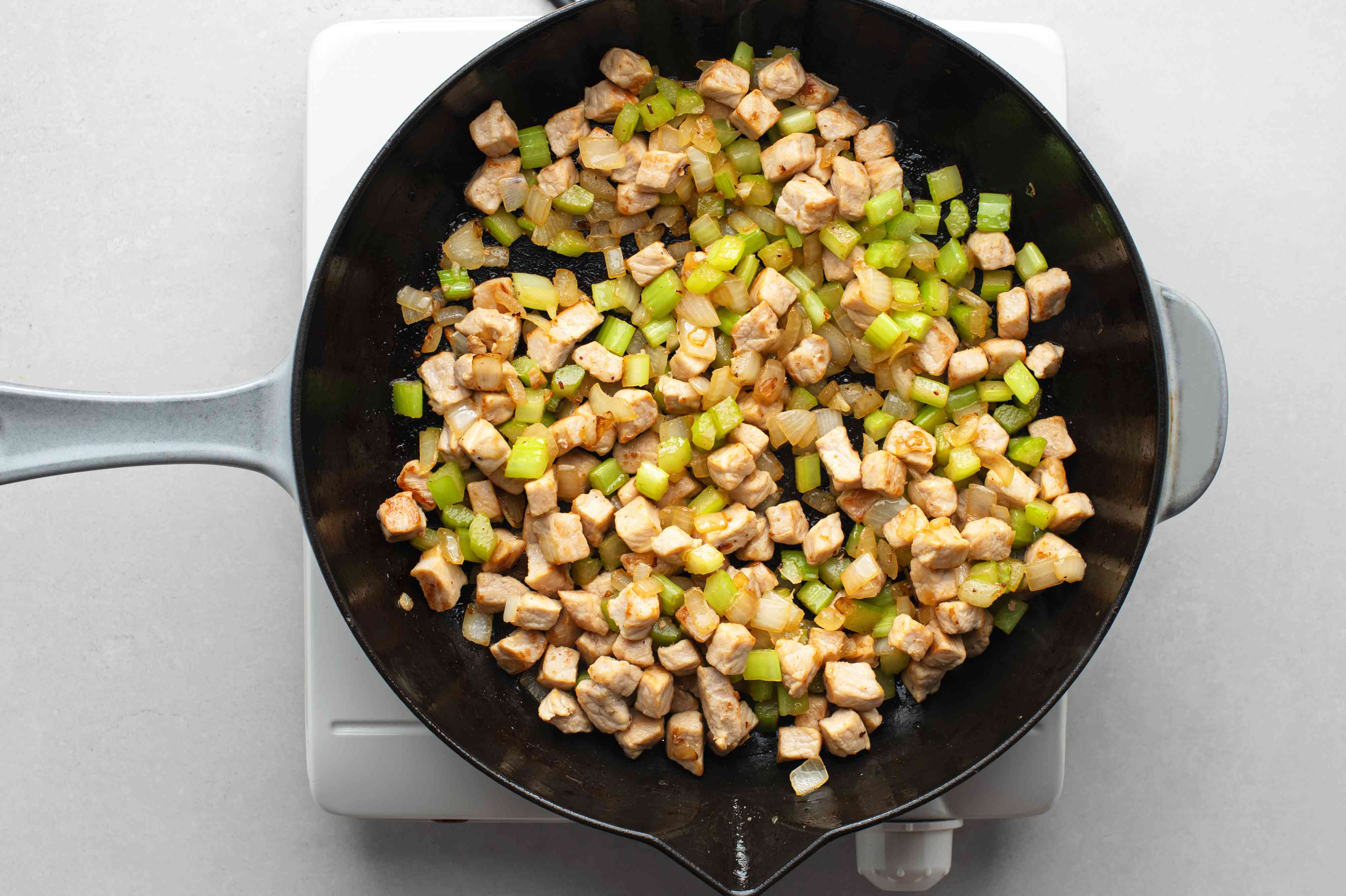 Add the chopped onion and celery to the pork in the skillet
