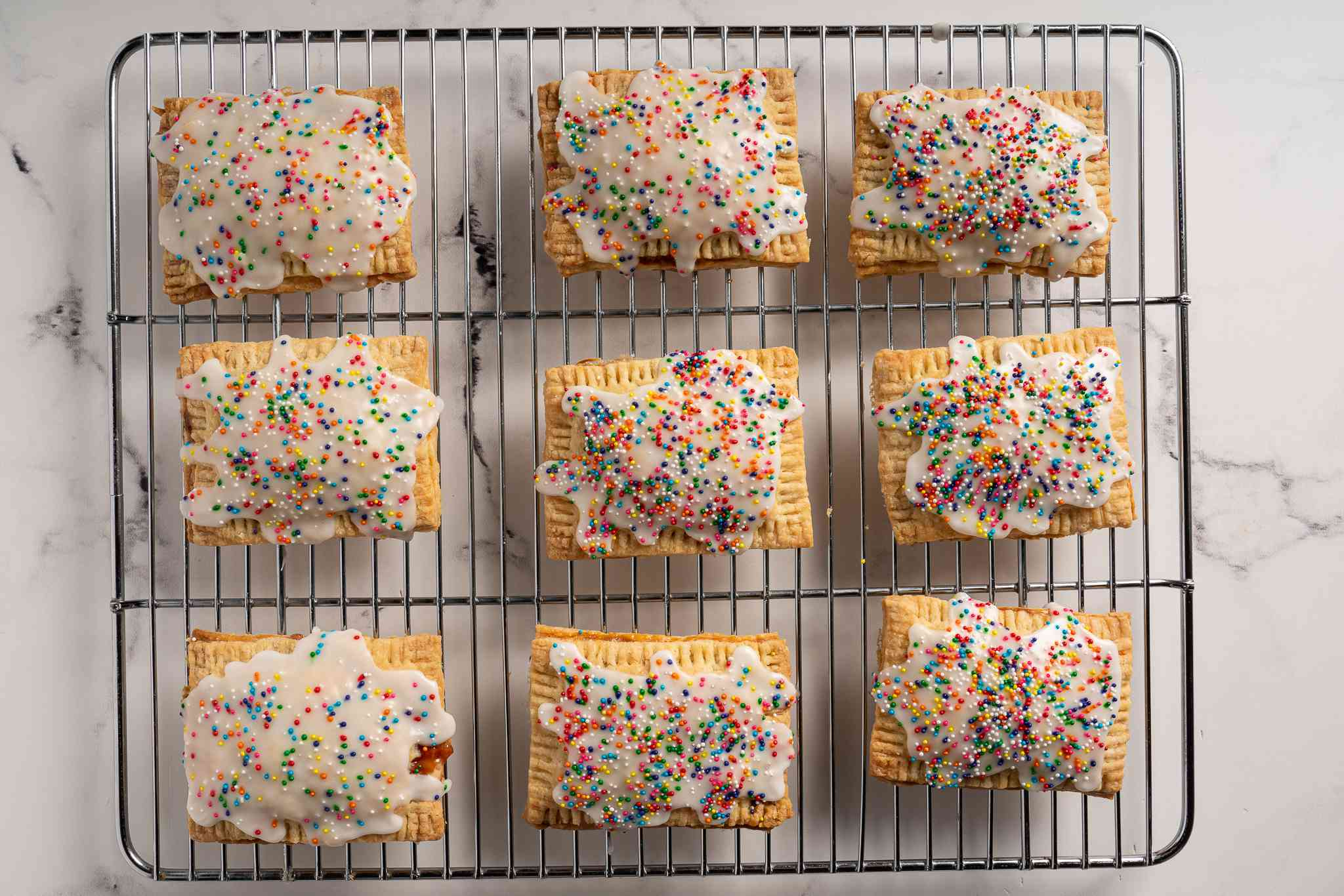 Homemade Pop Tarts on a cooling rack topped with sprinkles