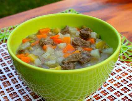Beef and vegetable soup in green bowl