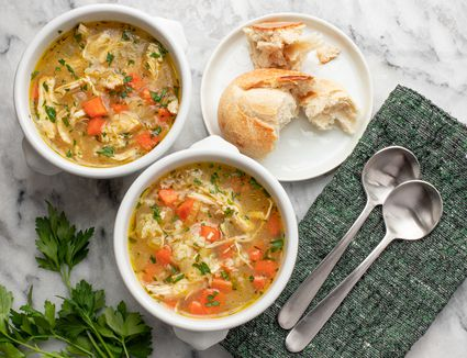Two bowls of Instant Pot chicken and rice soup with crusty French bread.