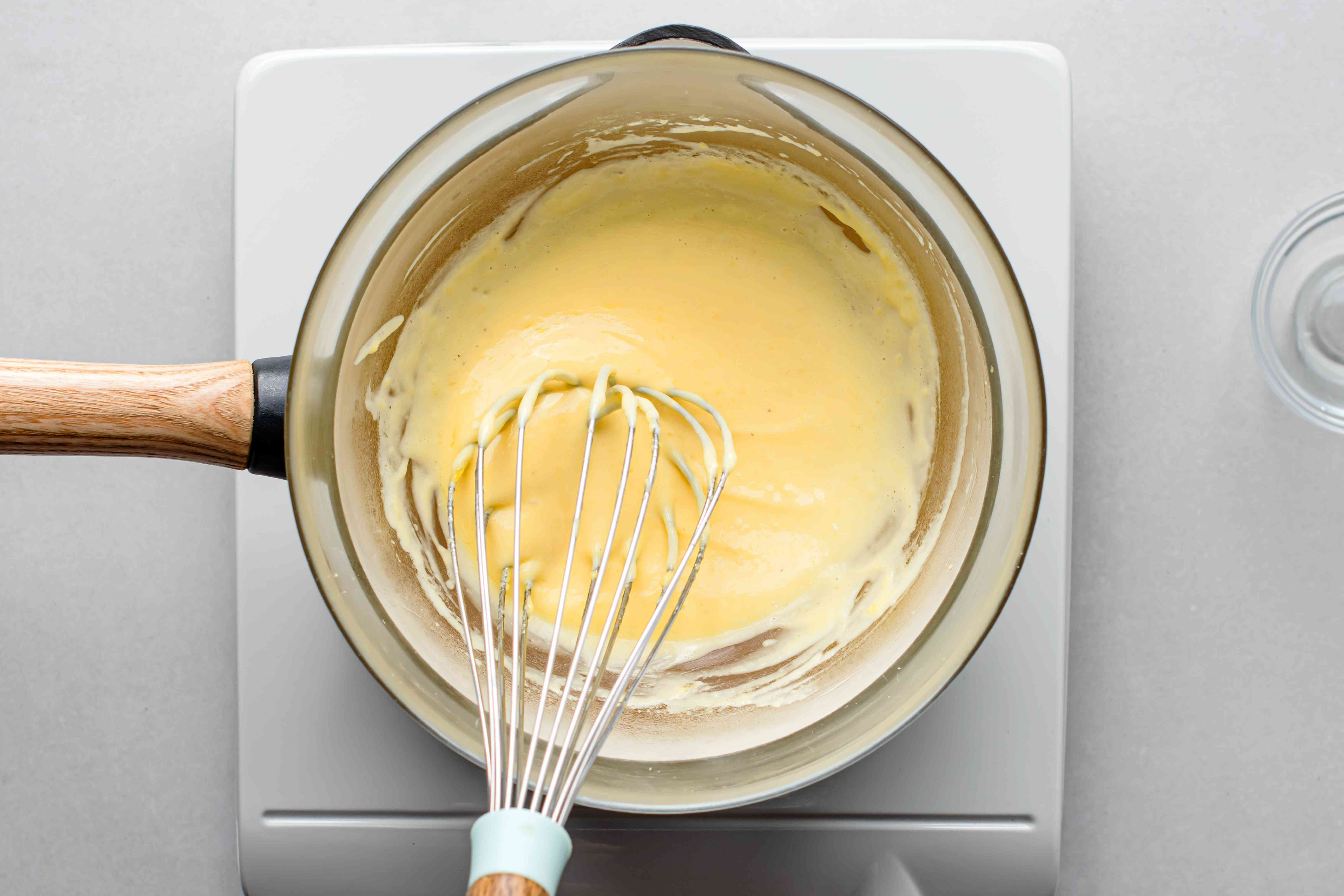 Hollandaise sauce mixture whisked over a double boiler