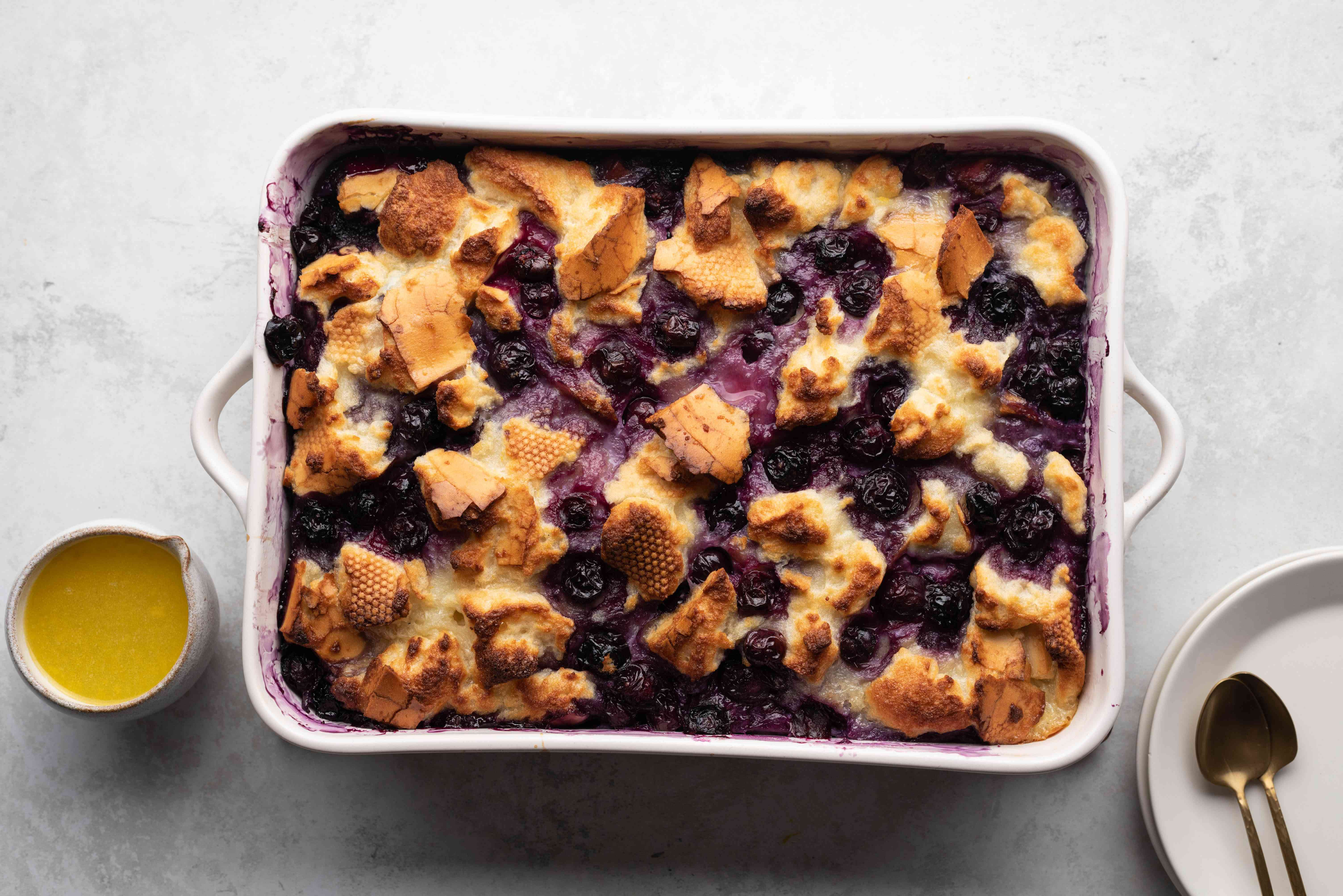 Blueberry Bread Pudding in a baking dish with lemon sauce on the side