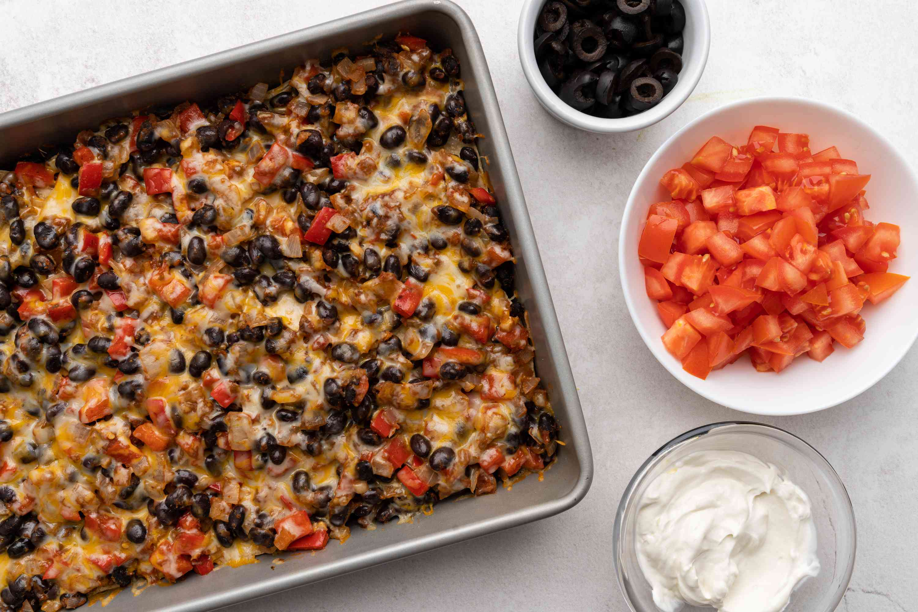 baked Vegetarian Mexican Casserole With Black Beans served with tomatoes, olives and sour cream