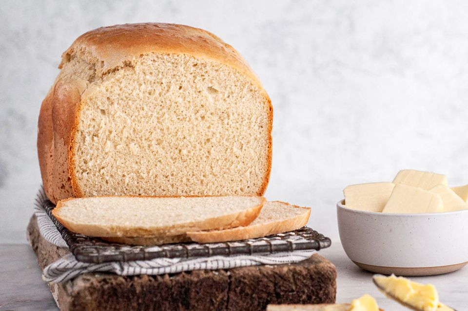 Bread Machine Country White Bread recipe, loaf of bread with slices of bread and butter in a bowl