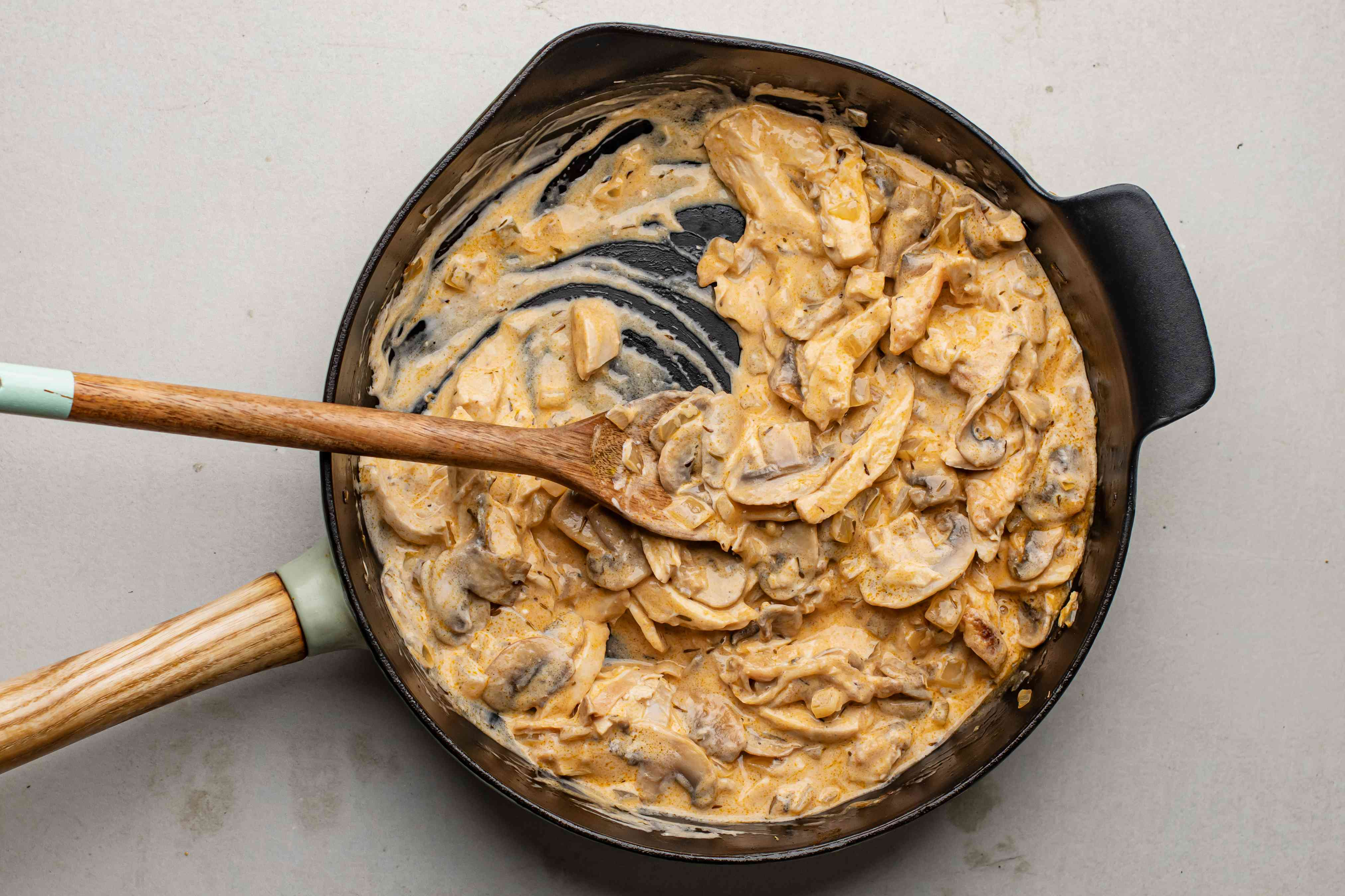Stirring sour cream into beef stroganoff