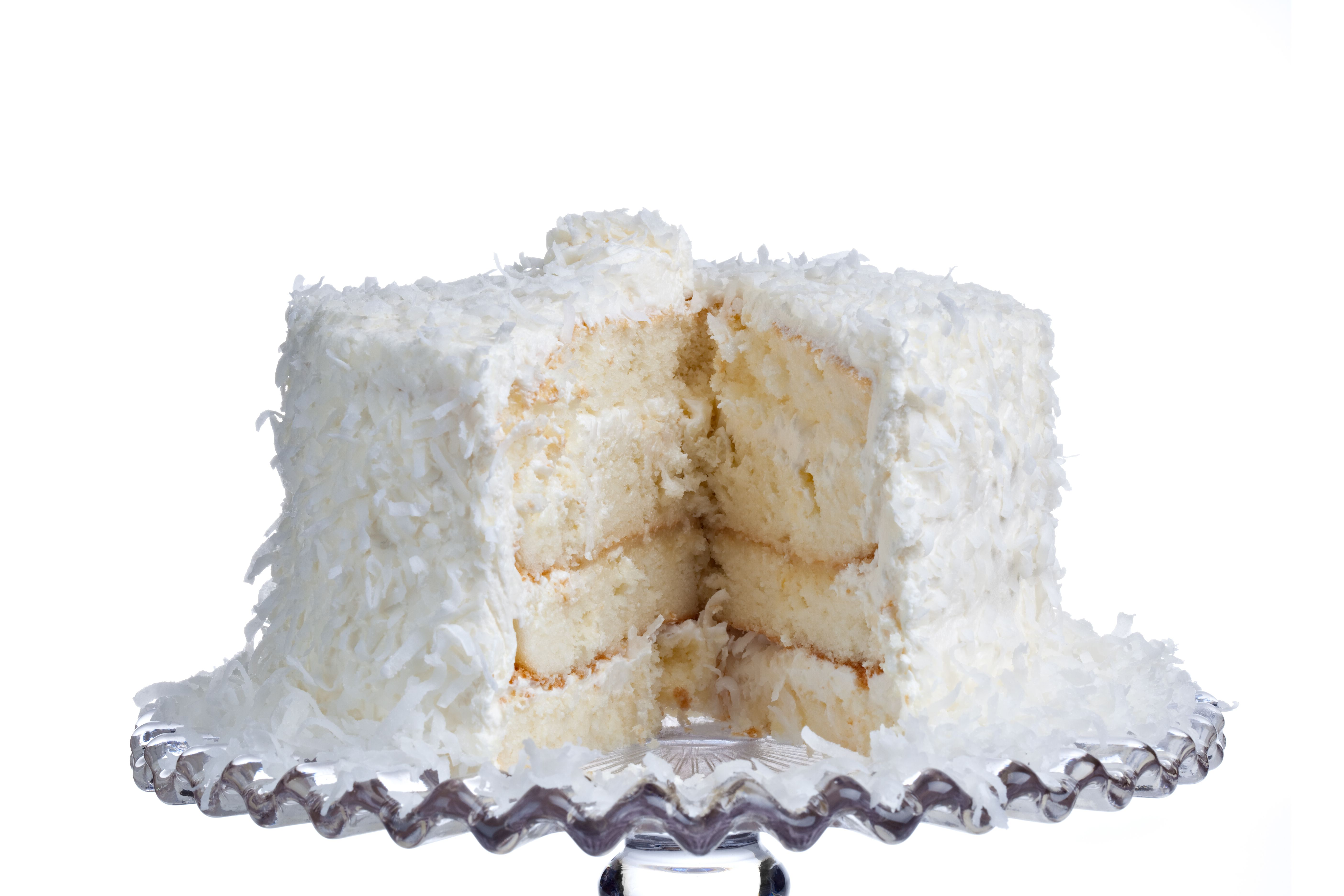 Layered coconut cake on a glass cake stand