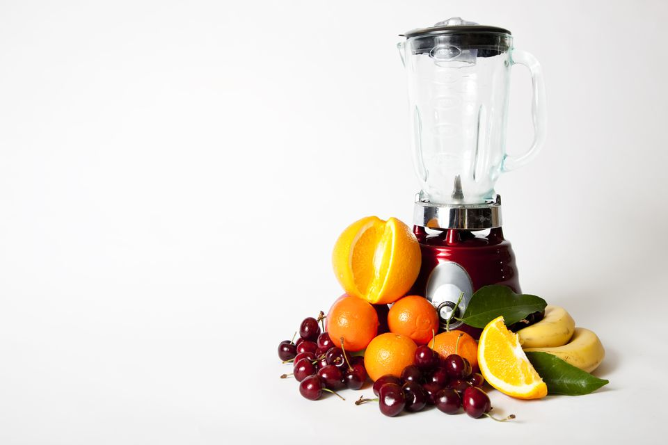 A blender surrounded by fruit