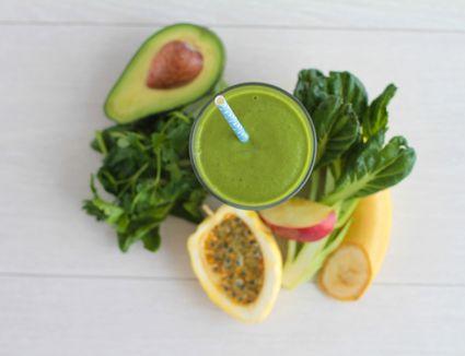 Green smoothie next to avocado, greens, apple and banana
