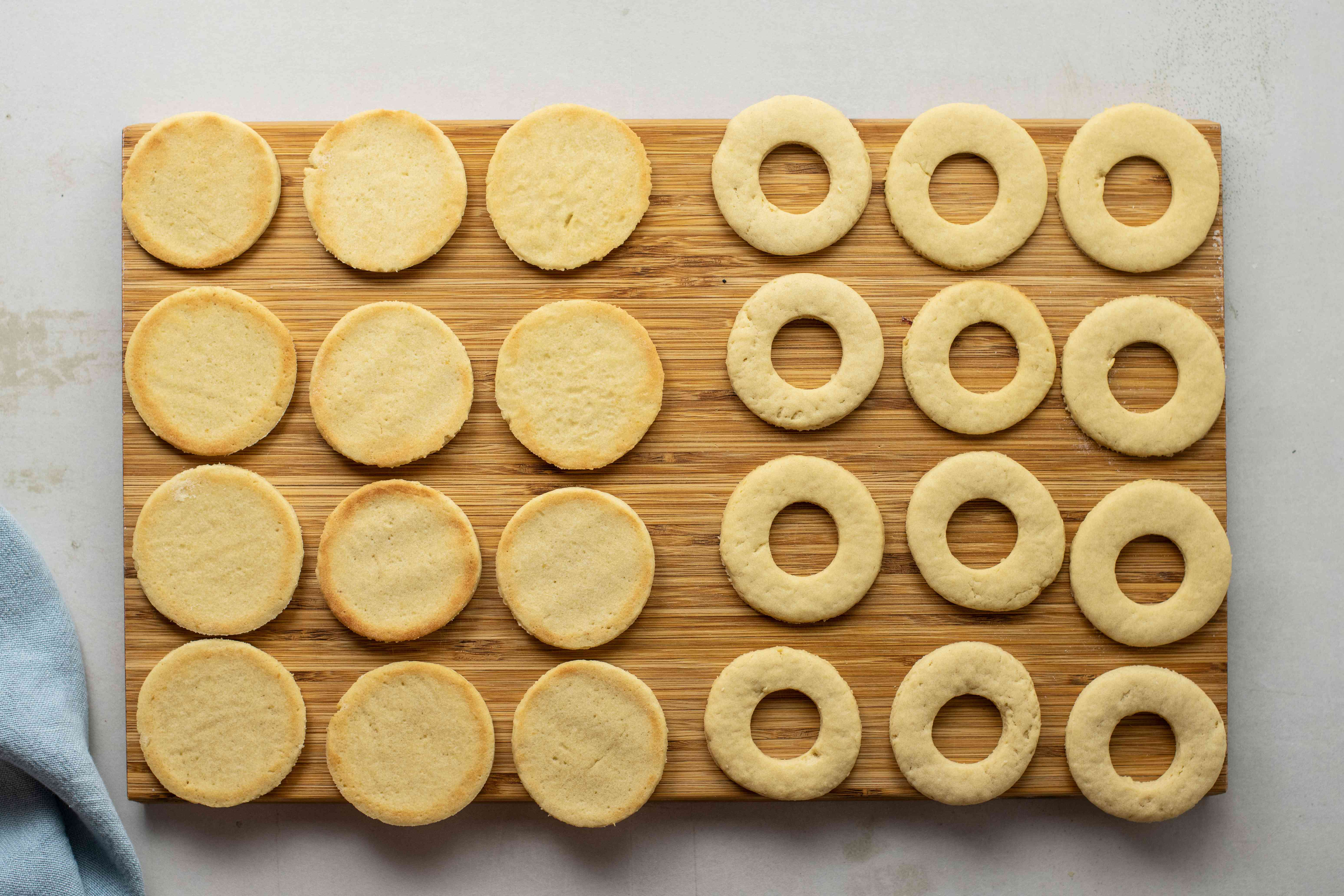 Baked maslenki cookies and holed-out tops of cookies on a wooden cutting board