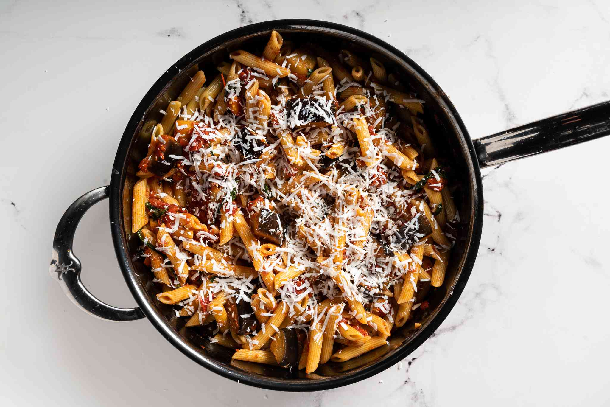 Pasta alla Norma in skillet topped iwth cheese