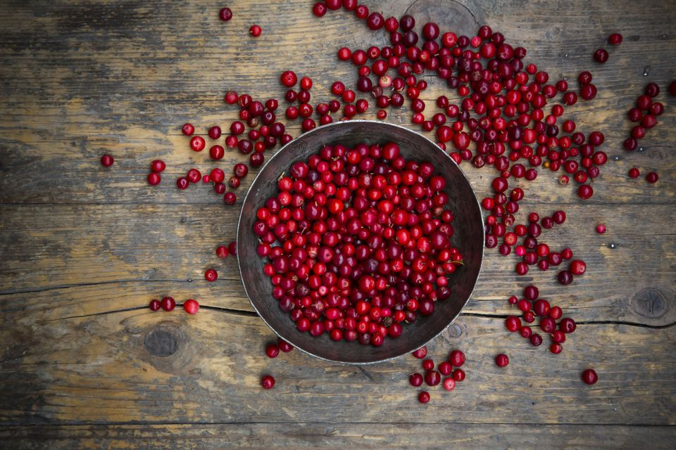 Lingonberries in a bowl and scattered on a wooden table