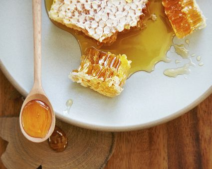 Natural honey comb on plate with spoon