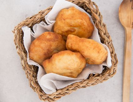 Native American fry bread in a basket along with a wooden spoon