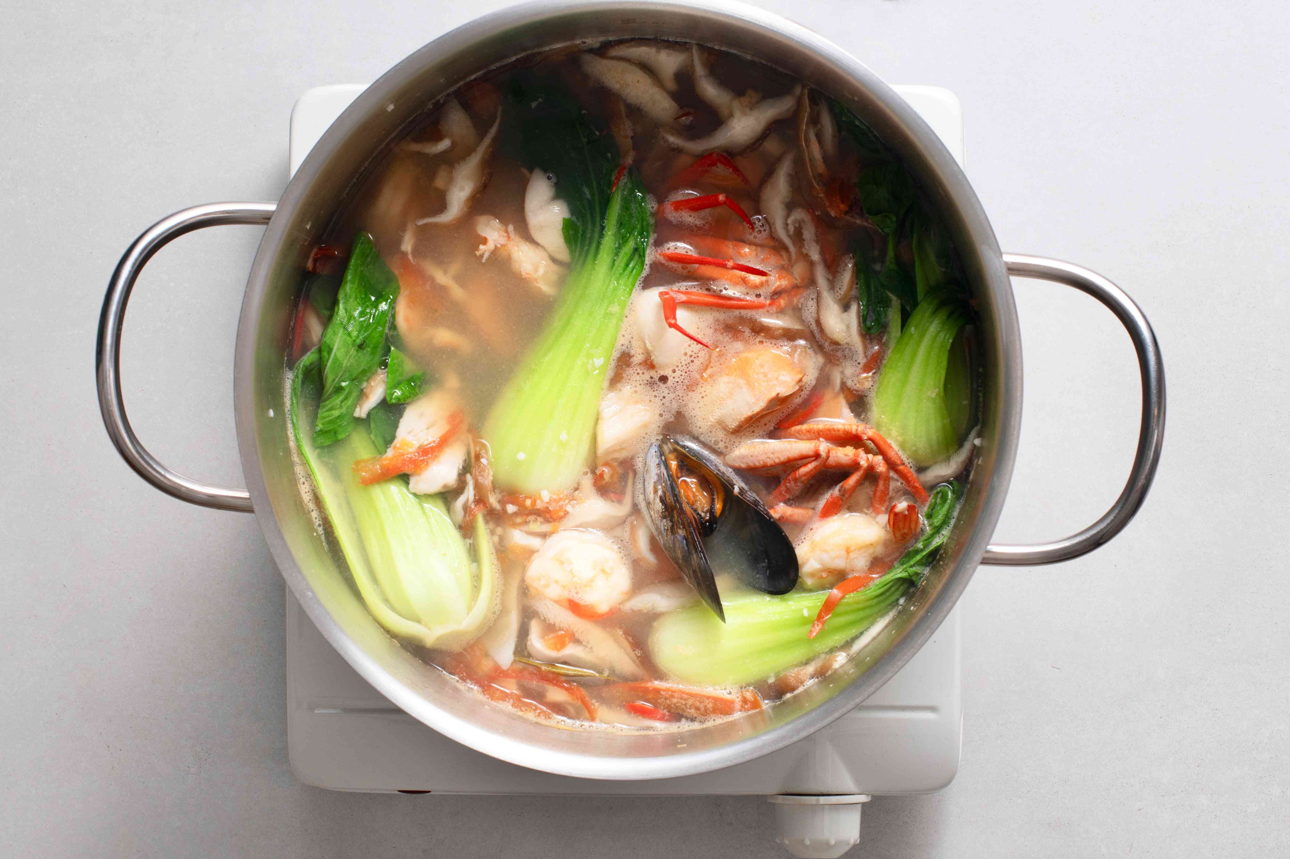 A pot of broth with bokchoy, mushrooms, seafood, and spices simmering