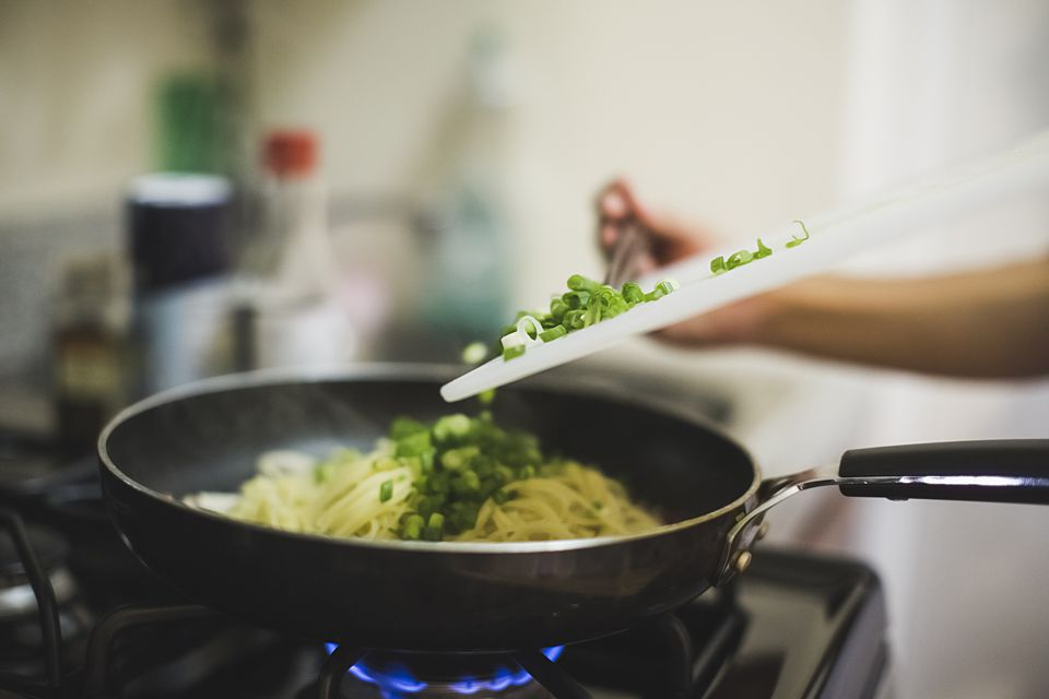 Young woman pouring shopped spring onions into frying pan