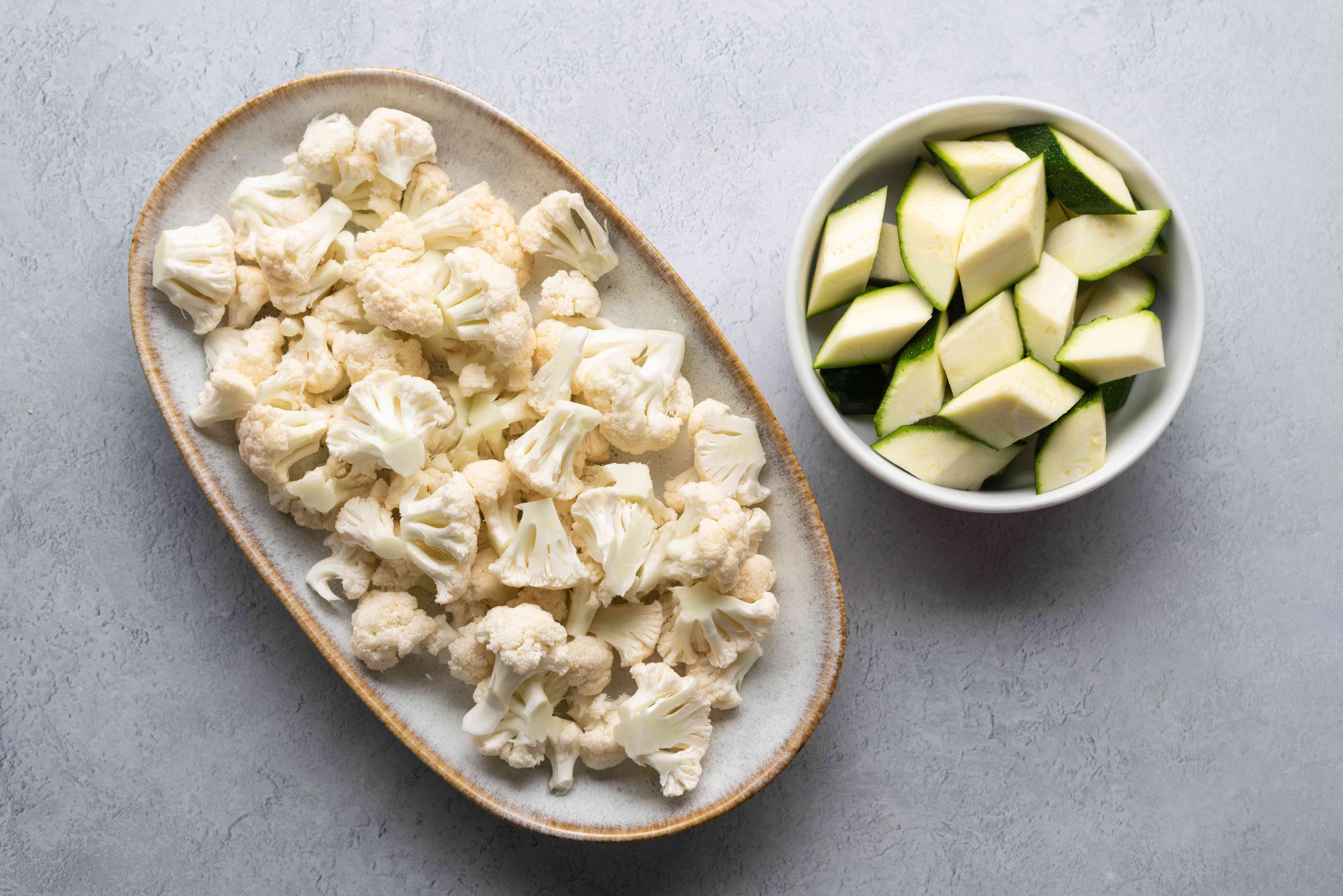 Cauliflower and zucchini pieces in bowls
