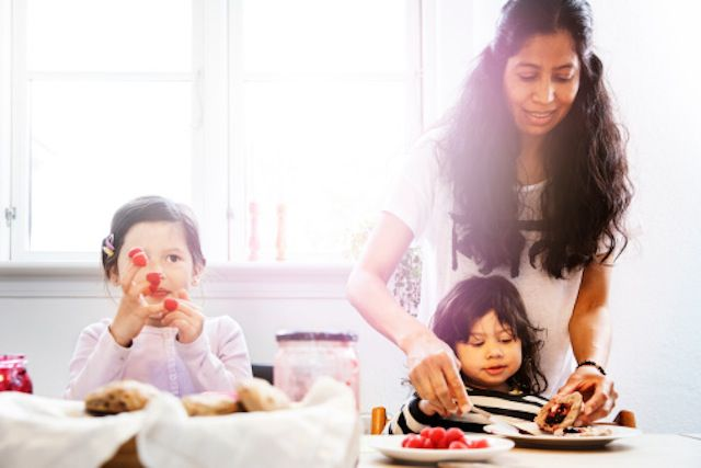Mother and 2 daughters eating breakfast