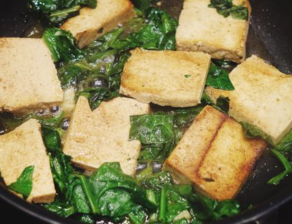Tofu and spinach in cooking pan