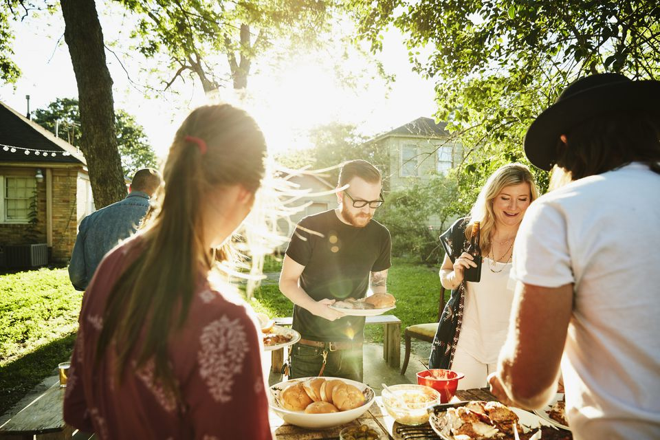 Group of friends serving themselves food in backyard on summer evening