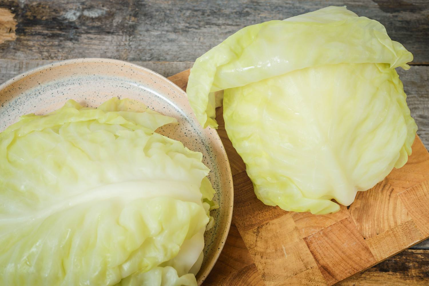 Boiled cabbage with the leaves removed on a cutting board