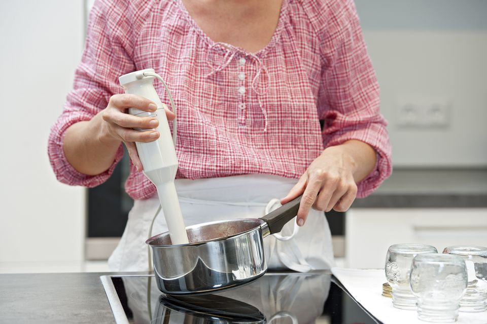 Woman using immersion blender in pot on stove