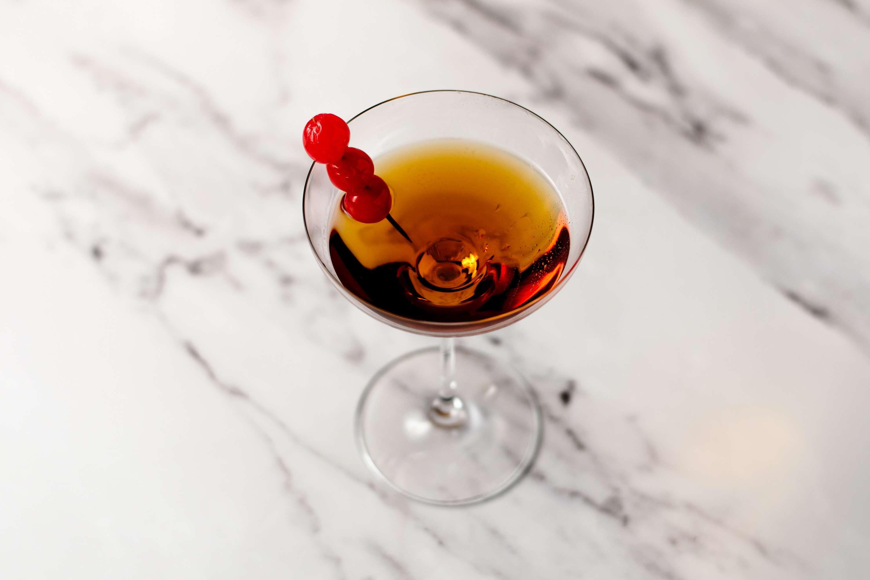 Classic gin & it cocktail with maraschino cherries