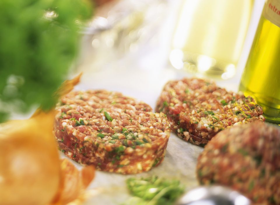 A plate of raw lamb burgers with herbs
