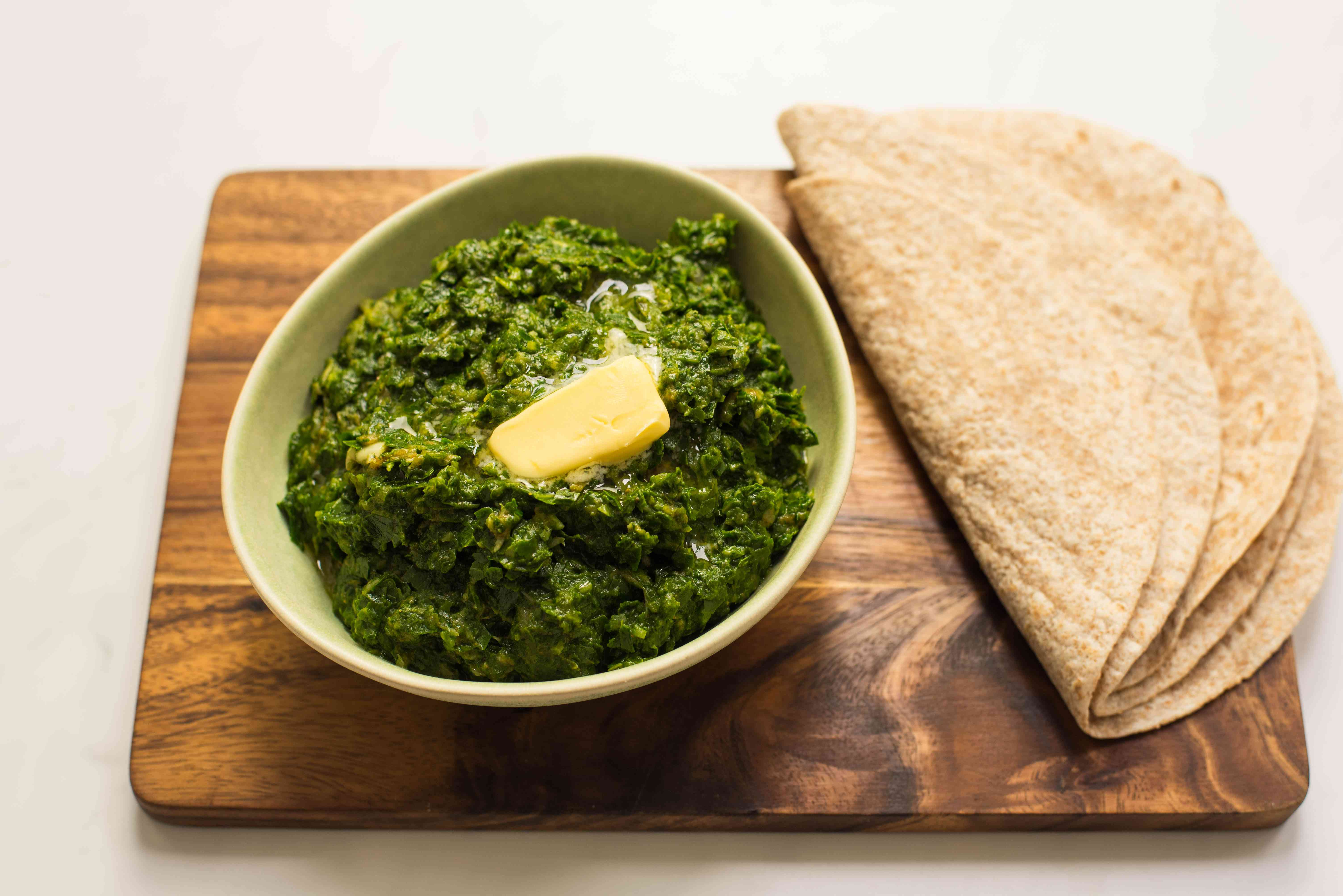 Saag garnished with butter with roti on the side