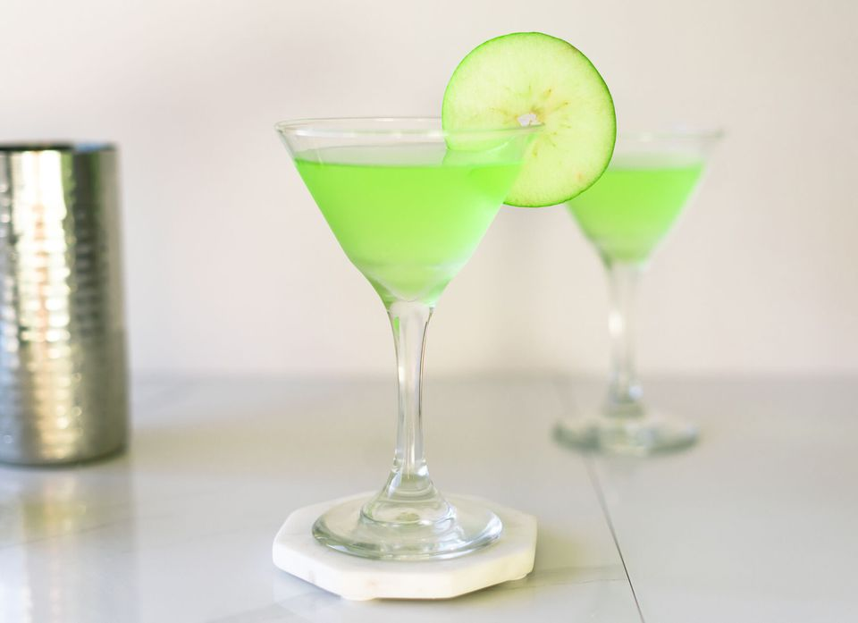 Green-colored apple martini with a sliced of green apple