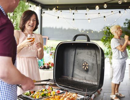 Man and woman laughing while barbecuing on patio at family lunch