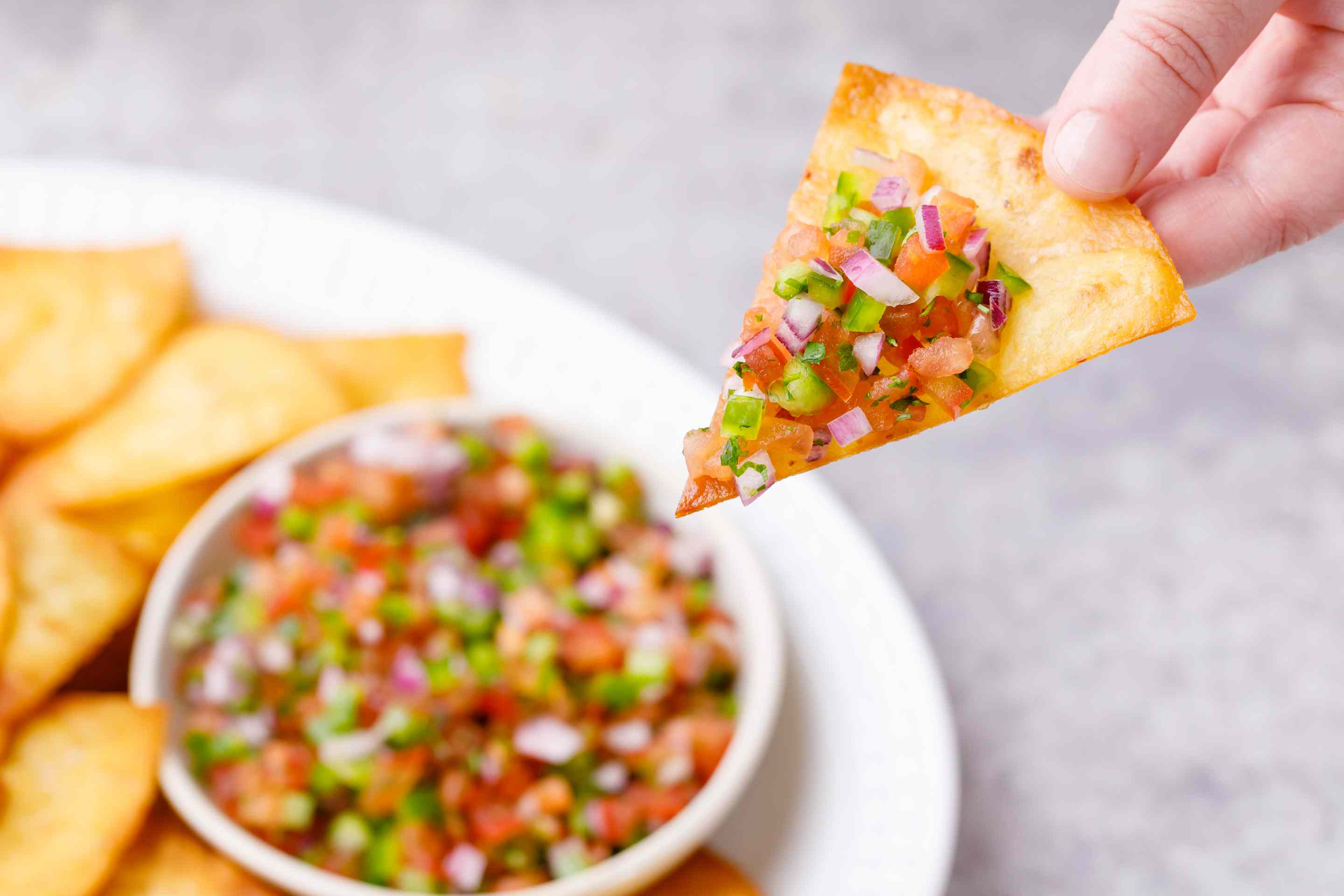 Person dipping the tortilla chip into salsa.