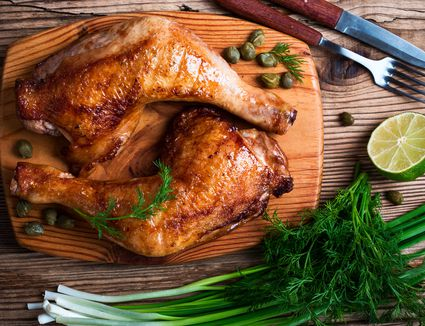 Two grilled chicken legs with onions and herbs