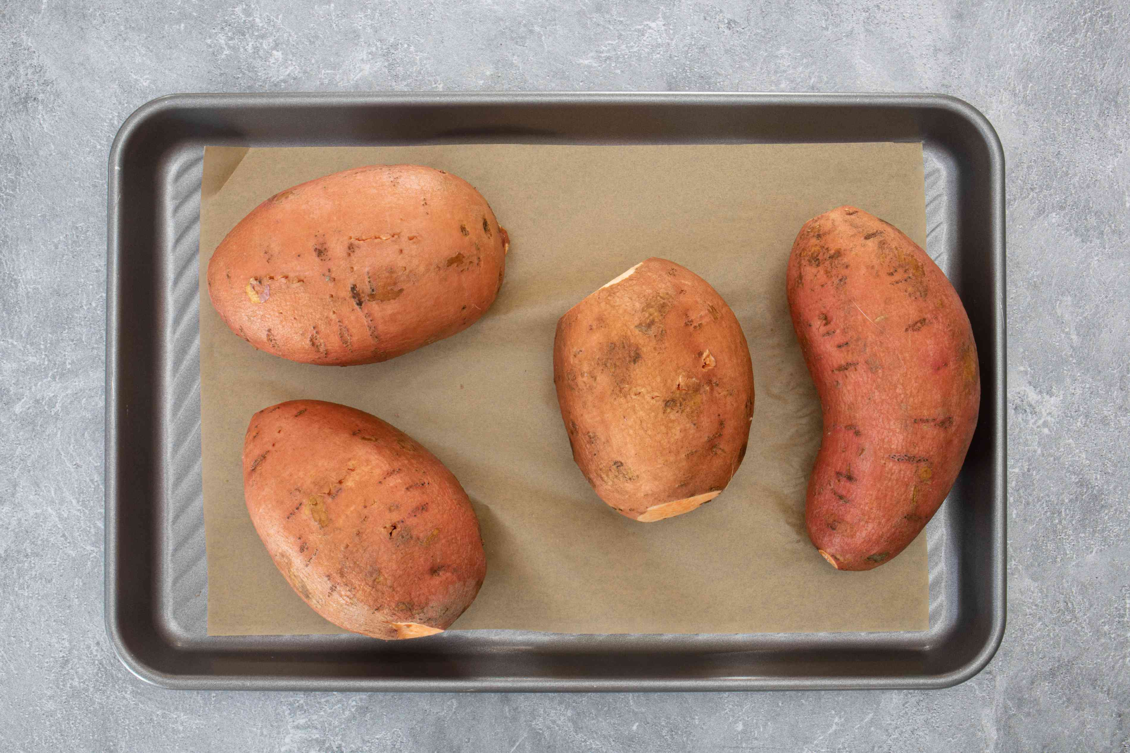 Scrubbed sweet potatoes on a lined rimmed baking sheet