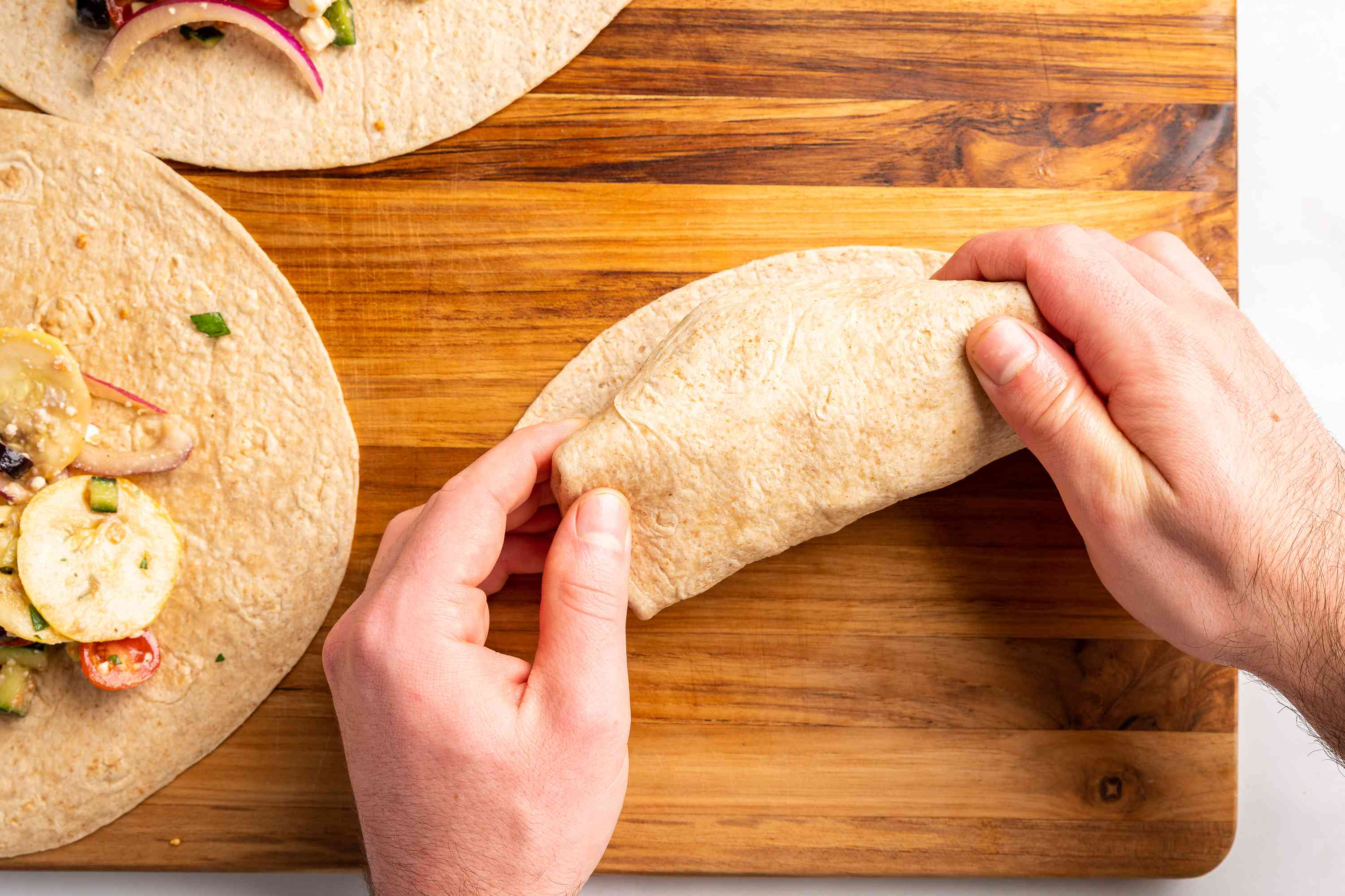 Hands rolling tortilla into complete wrap shape