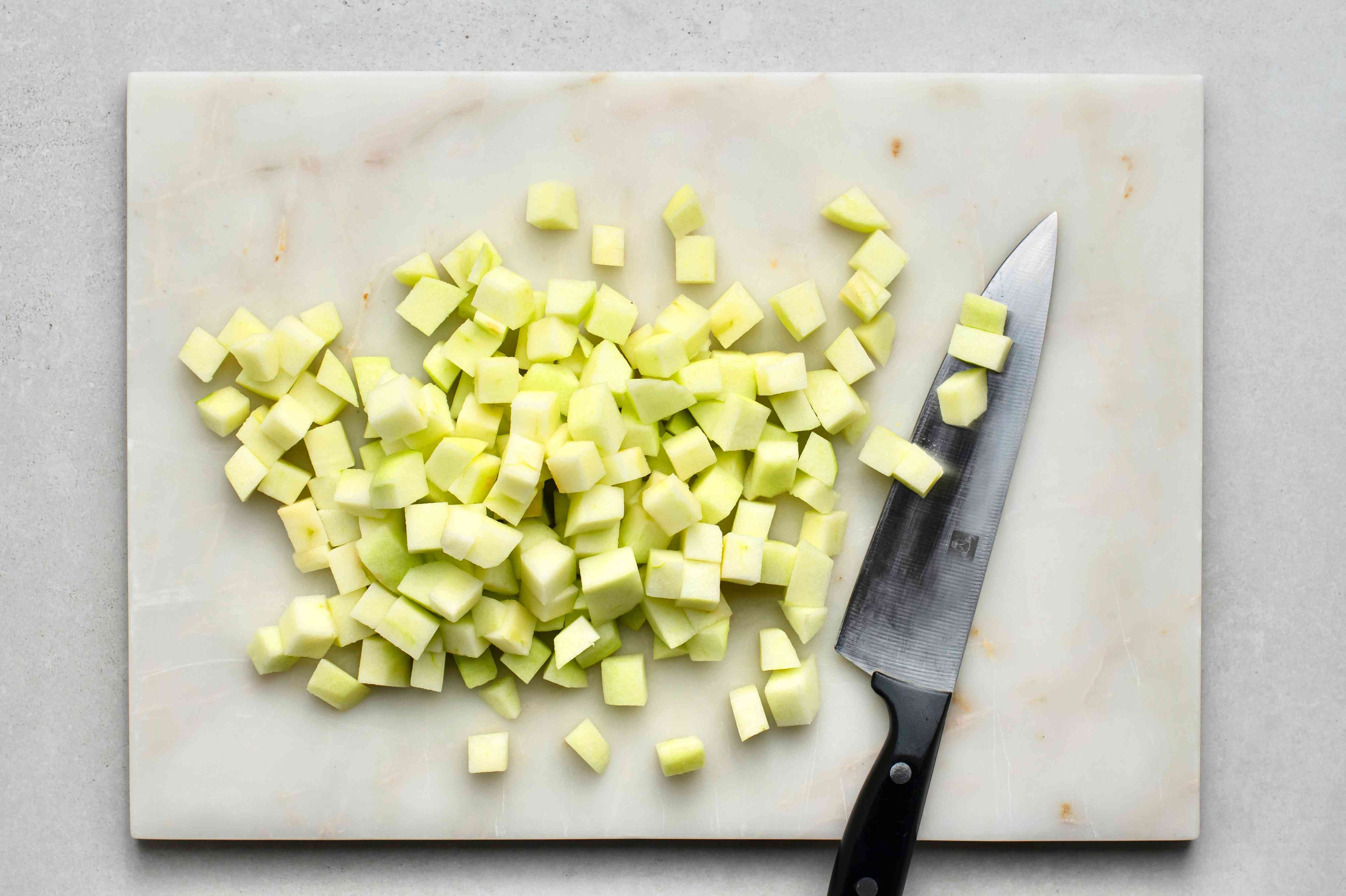 Peeled and chopped apples on a cutting board with a knife