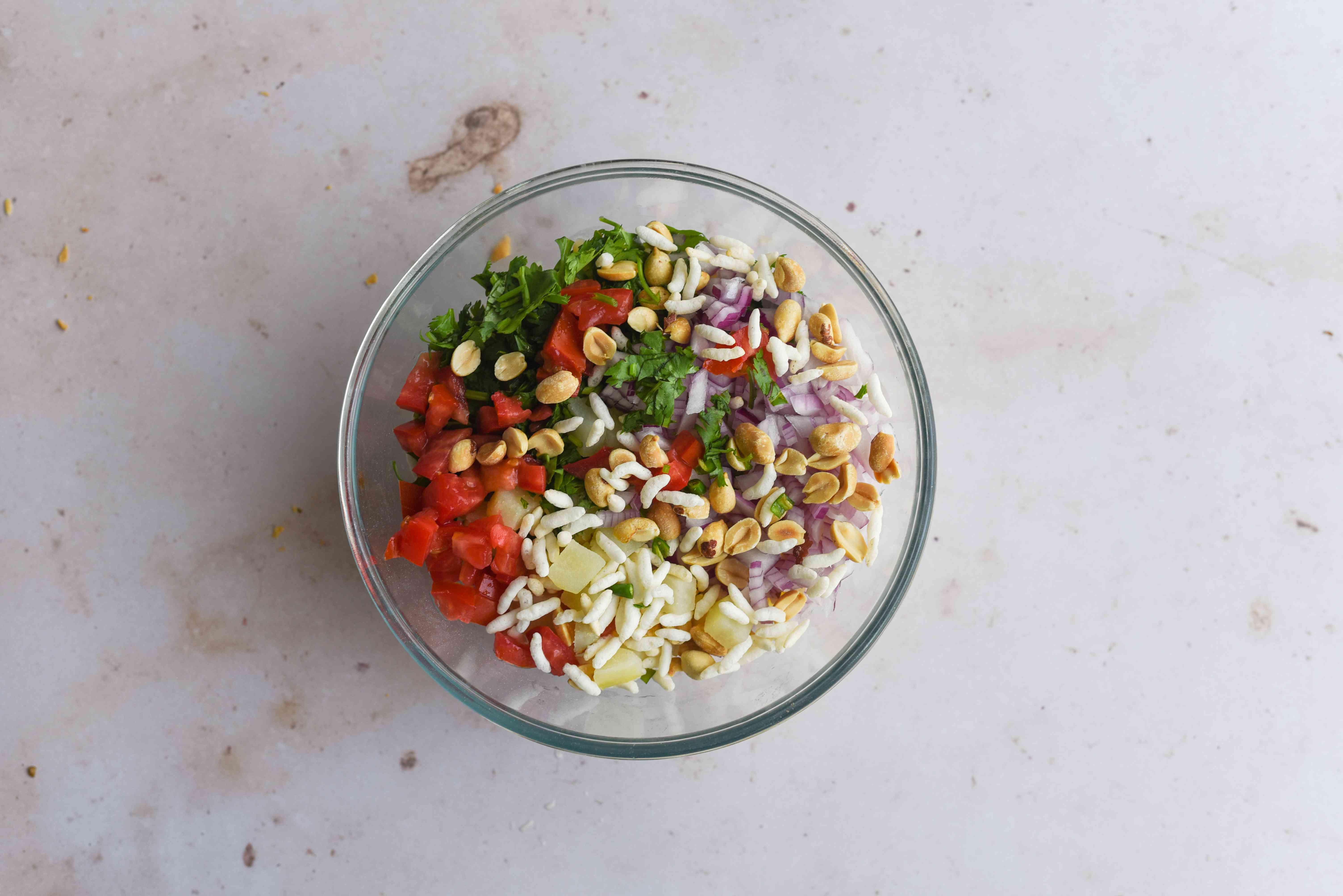 Mix the puffed rice, peanuts, potato, onion, tomato, coriander, and green chilies