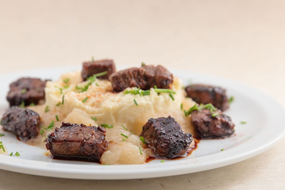 Served dish with marinated beaf, apple sauce and mashed potatoes.