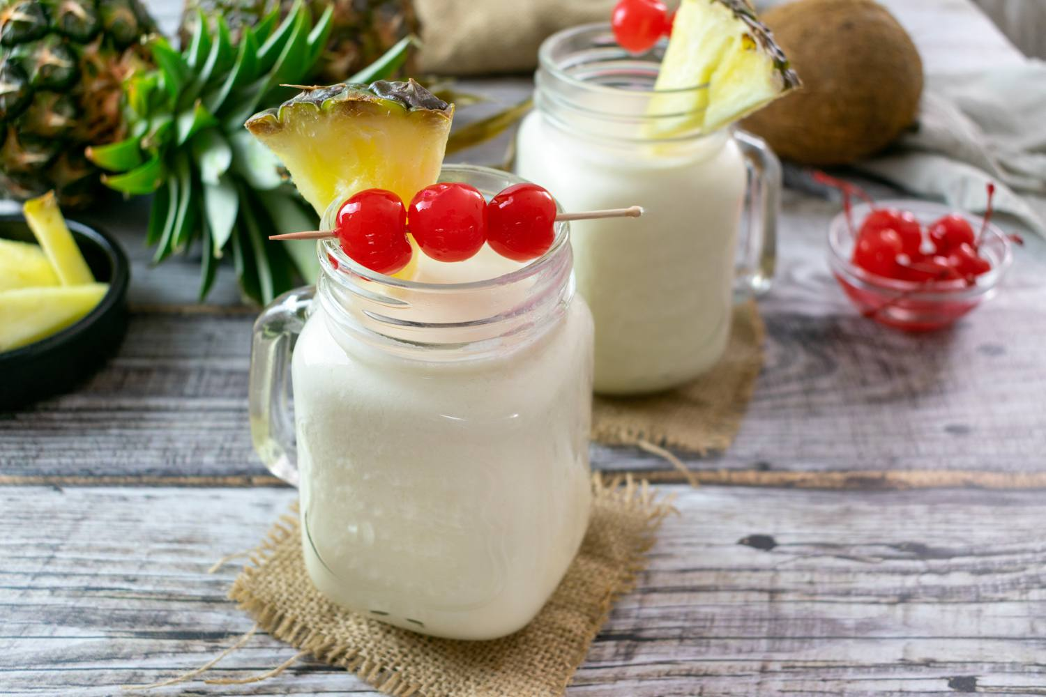 Two pina coladas with pineapple and cherry garnish