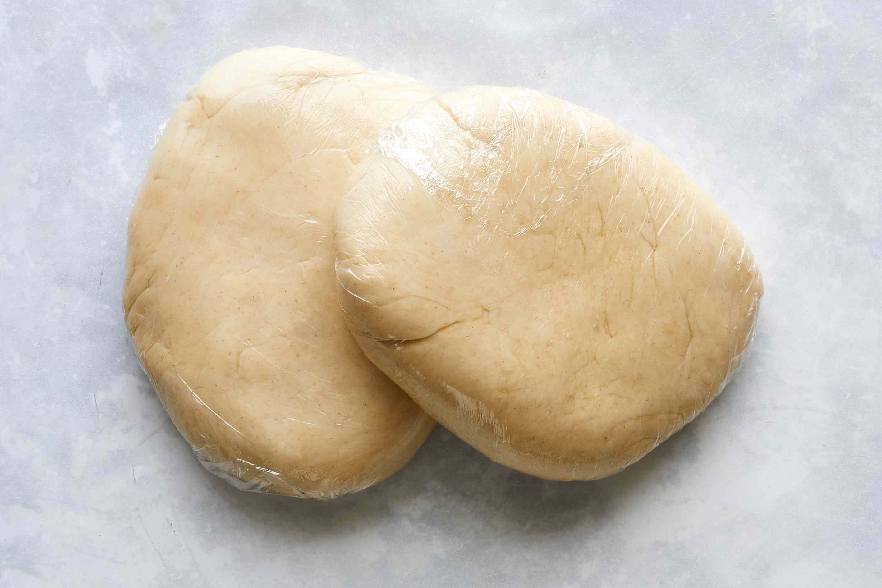 Balls of pie crust dough wrapped in plastic wrap