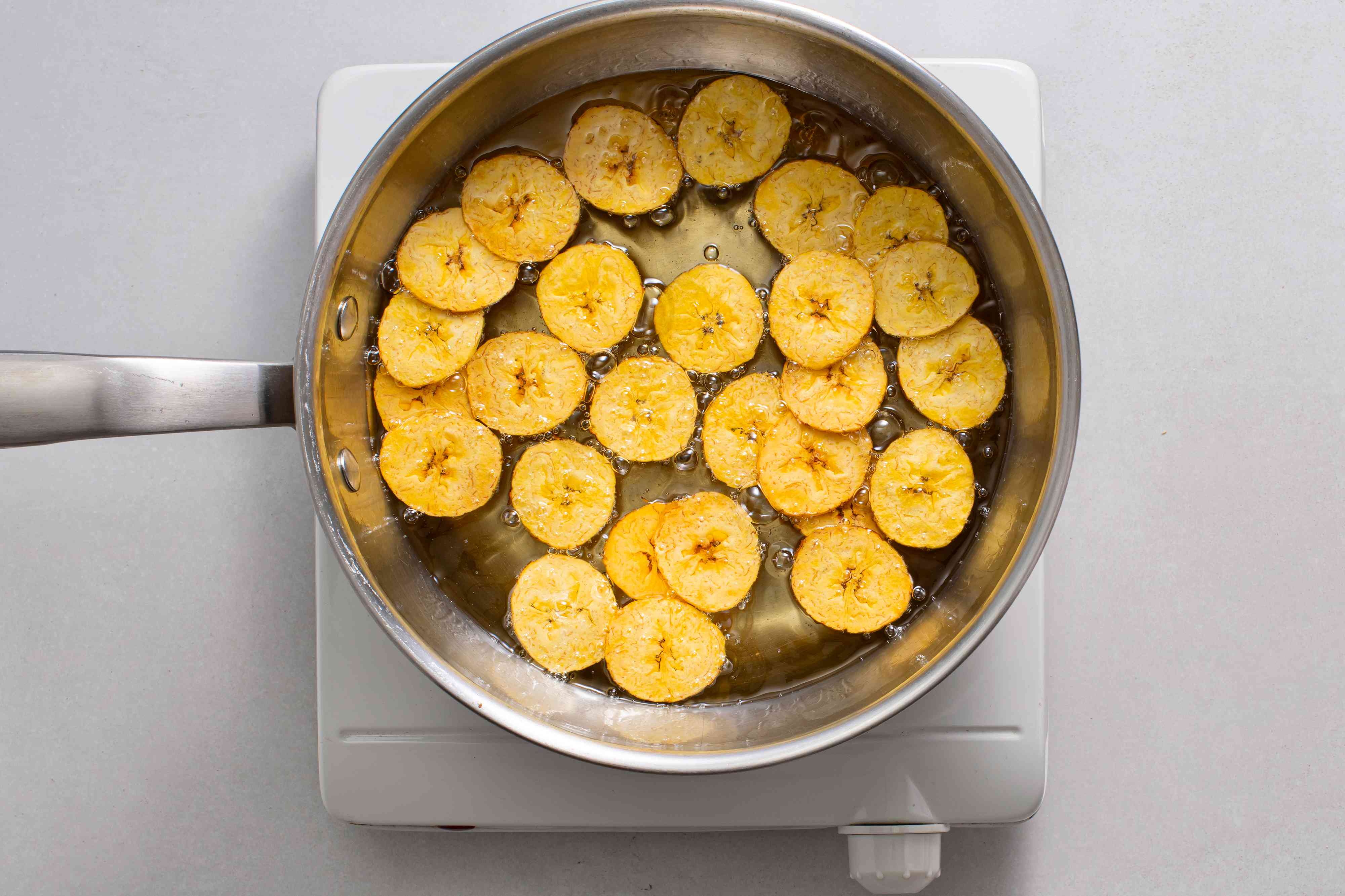 plantain slices frying in a pot of oil