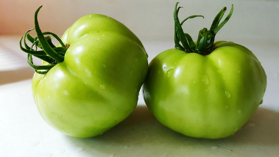 Close-Up Of Wet Green Tomatoes On Table