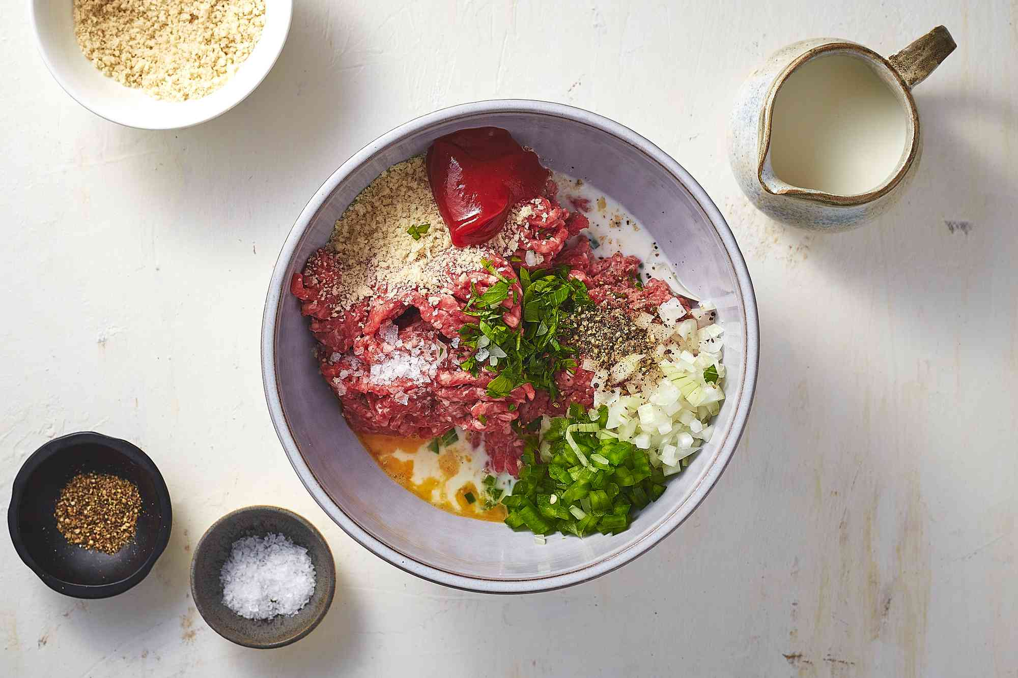 ground beef and pork with the milk, egg, breadcrumbs, onion, bell pepper, ketchup, parsley, salt, and pepper in a bowl