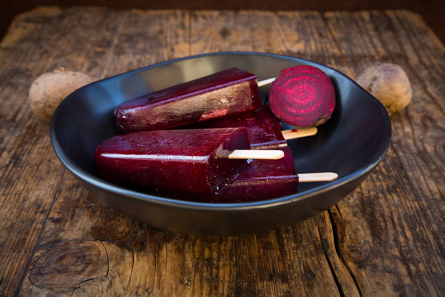 Bowl of homemade beetroot ice lollies on wood