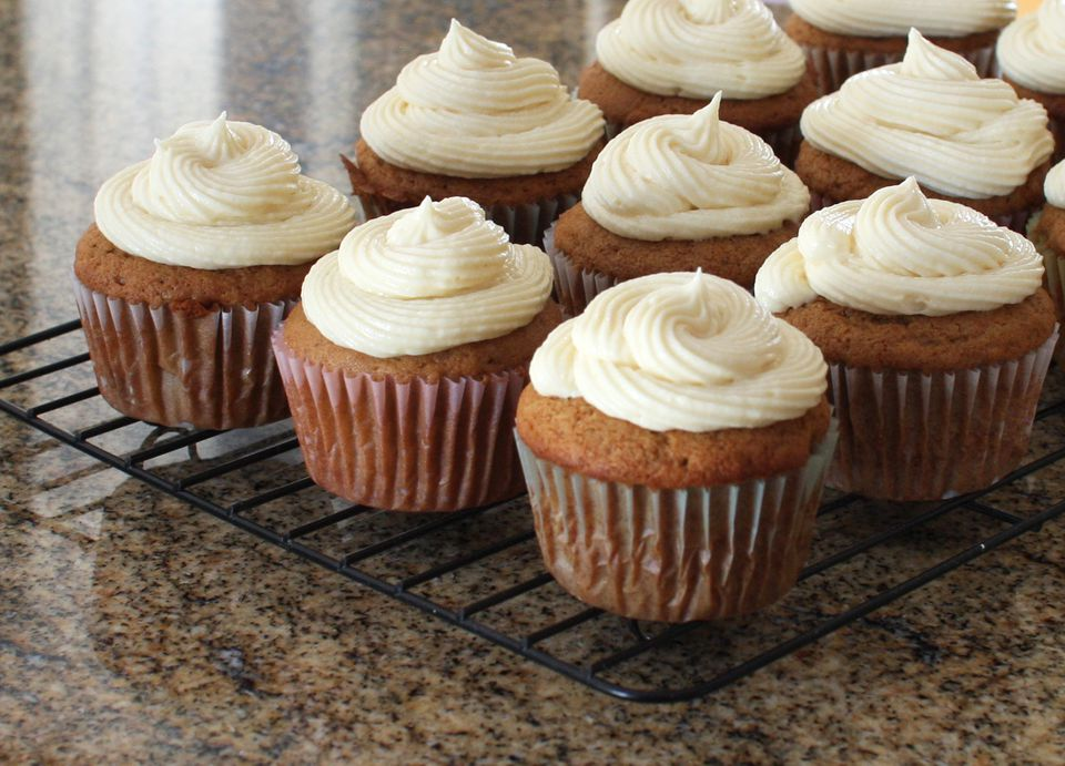 Frosted apple butter cupcakes on a rack.