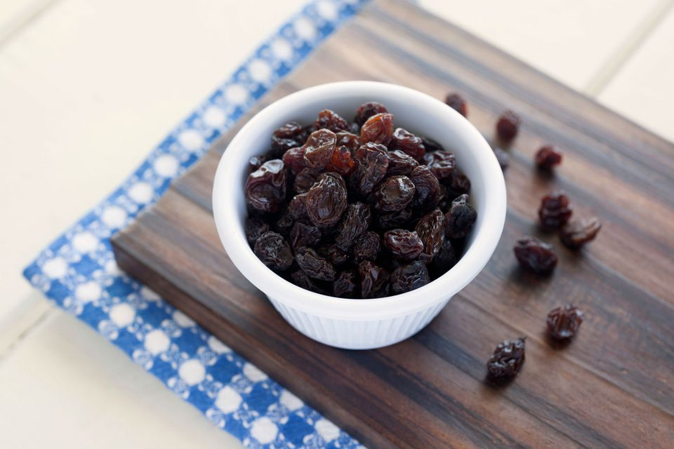 Close-Up Of Raisins In Bowl On Cutting Board