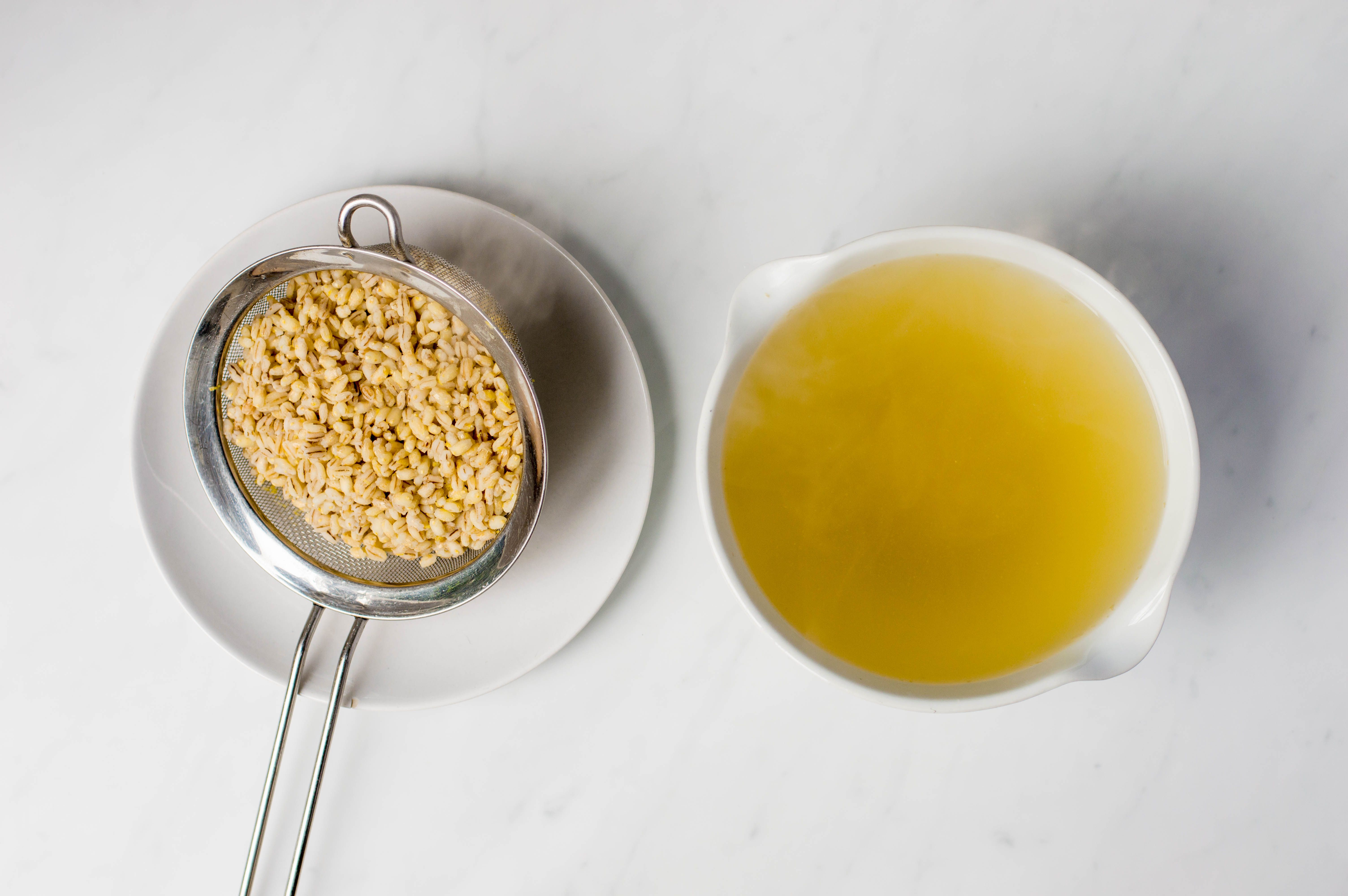 Barley in a colander next to strained liquid in a bowl